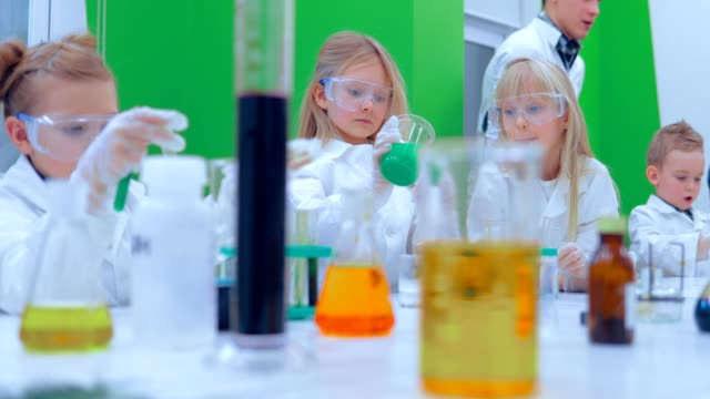 Children studing chemistry in school laboratory. Group of kids making experiments in chemistry class video