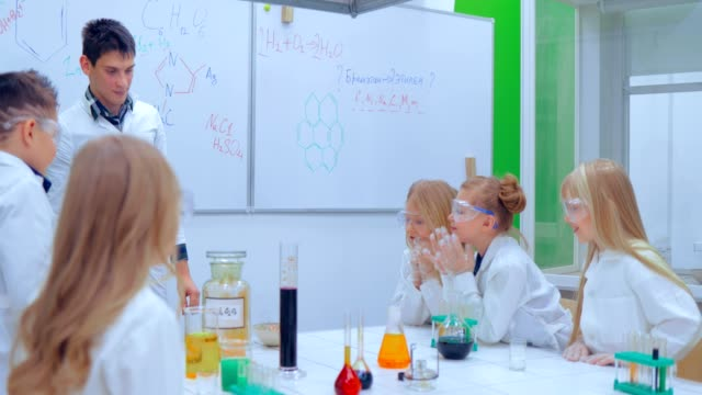 Children studing chemistry in school laboratory. Teacher and children in chemistry class video