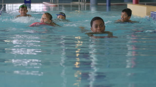 Children Swimming in a Pool at a Fitness Centre A small group of elementary aged children swim in a pool in a public gym. swimming stock videos & royalty-free footage