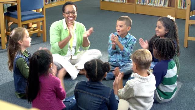 vidéos et rushes de enfants, professeur s'asseyant dans le chant de cercle et applaudissant - école primaire