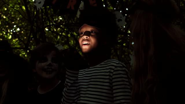 children telling spooky stories at halloween - four seasons filmów i materiałów b-roll
