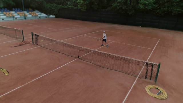 children tennis, skillful sports players teen boy and girl play tennis and ball throwing each other over net on red court - campionato video stock e b–roll