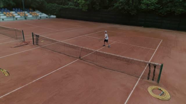 stockvideo's en b-roll-footage met kinderen tennis, bekwame sportspelers tiener jongen en meisje spelen tennis en bal gooien elkaar over netto op rode hof - kampioenschap