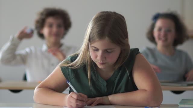 i bambini lanciano carta contro una ragazza. studentessa triste, vittima di aggressione, di nuovo a scuola. molestare a scuola. bullismo scolastico - preadolescente video stock e b–roll