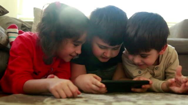 Children using digital tablet together in living room video