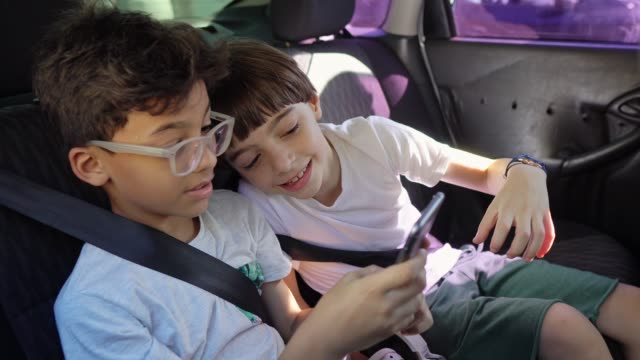 Children using smartphone on car trip