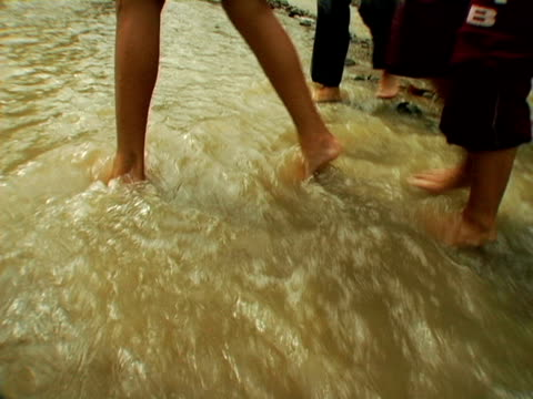 children wading across stream video