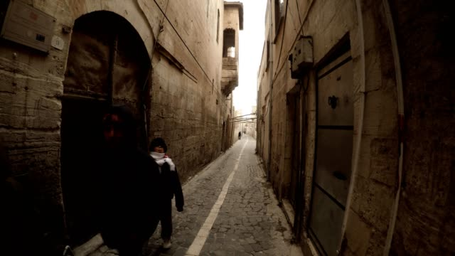 Children Walk on Narrow Ancient Street Paved with Stones in Urfa Antique Town of Prophets video