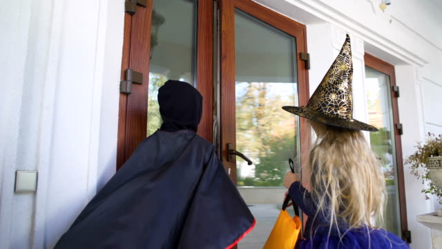 Children walk to neighbor house for sweets on Halloween, trick-or-treating