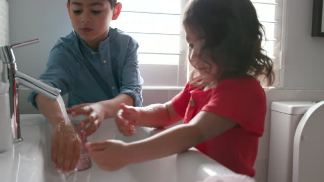 children washing their hands together at home - bagno domestico video stock e b–roll