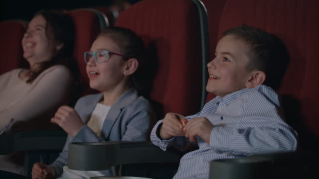 Children watching movie enthusiastically in cinema. Child entertainment concept Children watching movie enthusiastically in cinema. Happy boy and girl watching comedy film at cinema. Girl coughing in cinema. Young spectators enjoy fun cartoon. Child entertainment concept movie stock videos & royalty-free footage