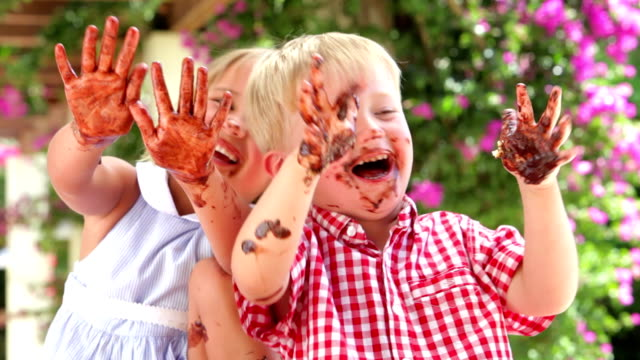 Children Waving Chocolate Covered Hands At Camera video