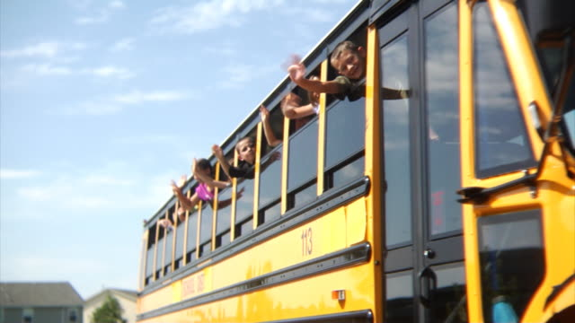 children waving from school bus - school buses stock videos and b-roll footage