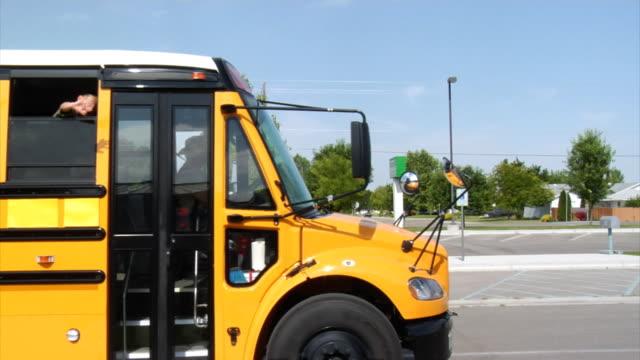 Children waving from school bus Children waving from school bus school buses stock videos & royalty-free footage