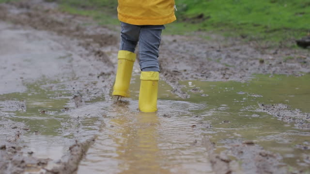 Children  wear yellow boot and They are walking on the muddy road