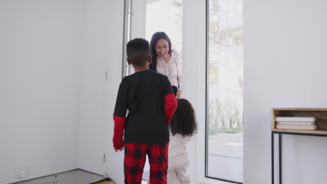 children wearing pajamas greeting and hugging working businesswoman mother as she returns home from work - pajamas stock videos & royalty-free footage
