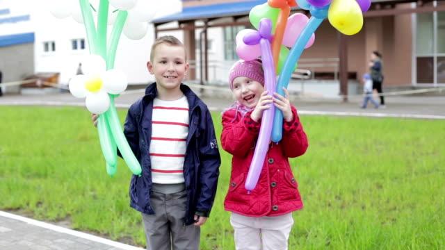 Kinder mit Luftballons in Form von Blumen. – Video