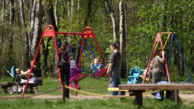 kinder mit ihren müttern, schwingende im park - kinderspielplatz stock-videos und b-roll-filmmaterial