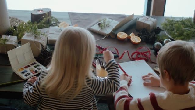stockvideo's en b-roll-footage met kinderen schrijven een brief aan de kerstman (slow motion) - christmas cabin