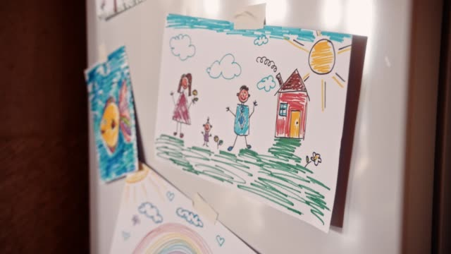 Children's colorful drawings on refrigerator door in family house kitchen Kid's drawings showing mother, father and child placed on fridge door in family house kitchen fridge stock videos & royalty-free footage