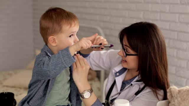 children's doctor examines the throat of a sick little boy with a wooden spatula - szpatułka przybór do gotowania filmów i materiałów b-roll