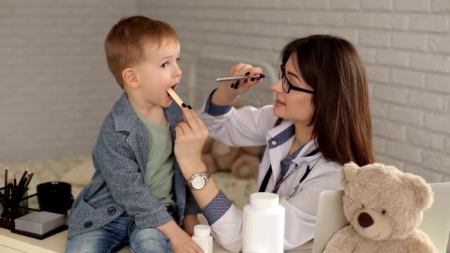 children's doctor examines the throat of sick boy. - szpatułka przybór do gotowania filmów i materiałów b-roll