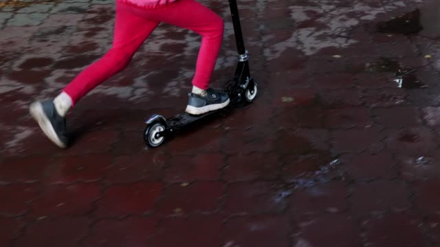 Children's feet ride on scooter through puddles, rain spray from fly on sidewalk video