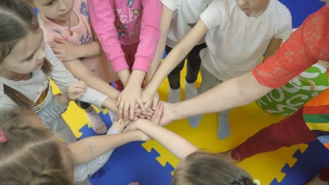 çocuk oyun odası. çocukların elleri birbirlerinin üstünde. - kesit stok videoları ve detay görüntü çekimi
