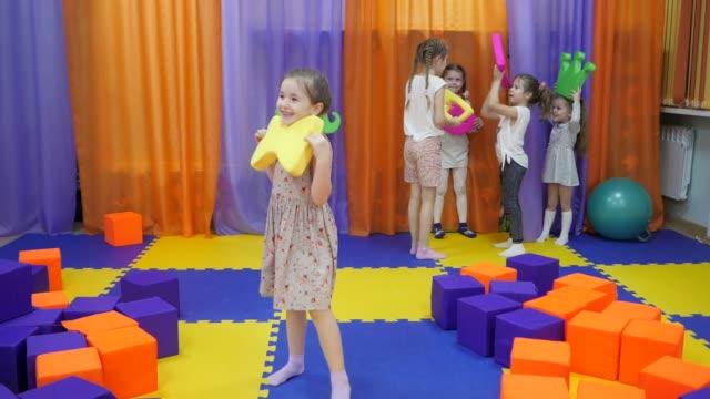 children's playroom. little girls defile with soft toys. - class стоковые видео и кадры b-roll