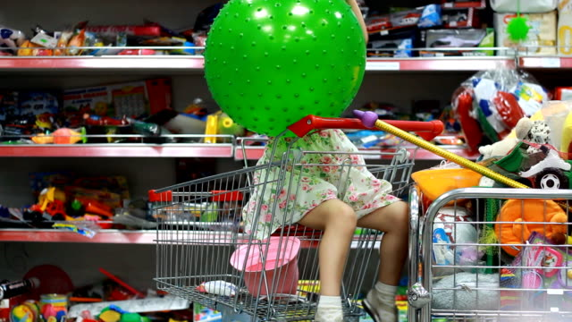 children's shop with toys. a child in a supermarket sits in the shopping cart and plays with a green ball. - sprzęt sportowy filmów i materiałów b-roll