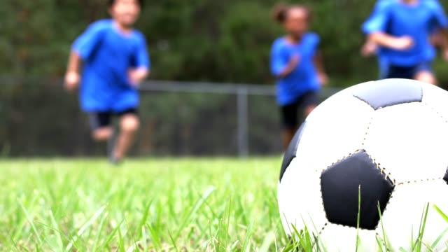 Children's soccer team players run toward ball on playing field. video