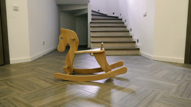 Children's wooden horse stands in the middle of the house