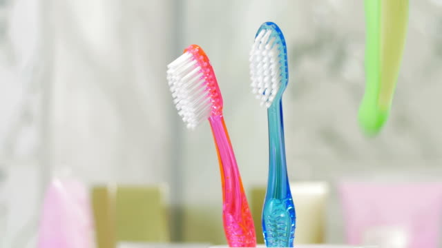 vídeos de stock e filmes b-roll de childs e adultos escovas de dentes no copo - escovar