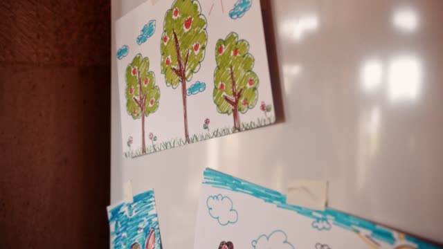 Child's drawings of family placed on fridge door at home Kid's colorful sketches of family, fish, trees and rainbow placed on kitchen refrigerator fridge stock videos & royalty-free footage