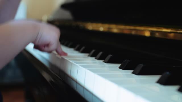 des kindes finger drücken der tasten eines klaviers - schlüssel videos stock-videos und b-roll-filmmaterial