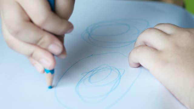 child's hand drawing dinosaur on white paper. - kids holding hands filmów i materiałów b-roll