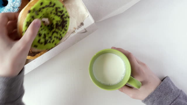 Child's hand takes a donut out of the box. Top view