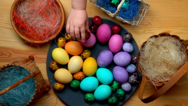 Child's hand takes and lays colored easter eggs in different baskets video