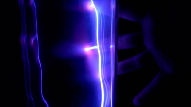 Child's hand touches the plasma tube with lightning in the dark. Child's hand touches the plasma tube with a dark blue lightning in the dark. Exhibition at the Museum of cosmonautics. high voltage sign stock videos & royalty-free footage