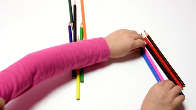 Child's hand turned the pencils in their hands and collected the whole set of pencils video