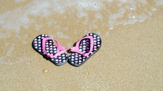 Child's shoes on the beach. Child's shoes on the beach. Beach shoes in the sea wave. baby booties stock videos & royalty-free footage