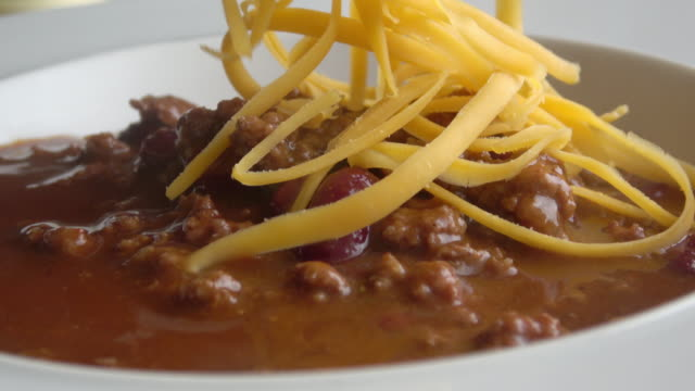 Chili Bowl Close-up on Chili Bowl with Onion, Cheddar Cheese, and Garnish chili pepper stock videos & royalty-free footage