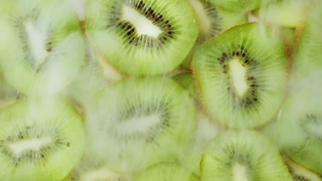 kylda kiwiskivor med kall ångrök. närbild av grön saftig konsistens med frön av exotisk frukt. begreppet hälsosam mat, vegan ekologisk näring. färgstark bakgrund. - kiwifrukt bildbanksvideor och videomaterial från bakom kulisserna
