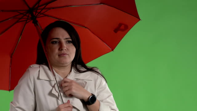 Chilled woman under red umbrella adjusting her coat against green screen video