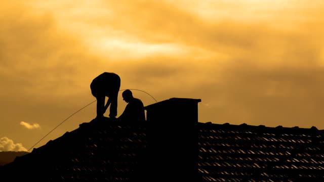 skorstenen rengöring och reparation vid solnedgången - yttertak bildbanksvideor och videomaterial från bakom kulisserna