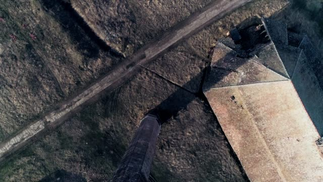 Chimney old made of bricks. Heli aerial drone shot rising revealing landscape. Sunny, clouds.