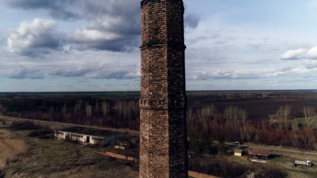 Chimney old made of bricks. Heli shot rising, revealing landscape. Sunny weather, some clouds.