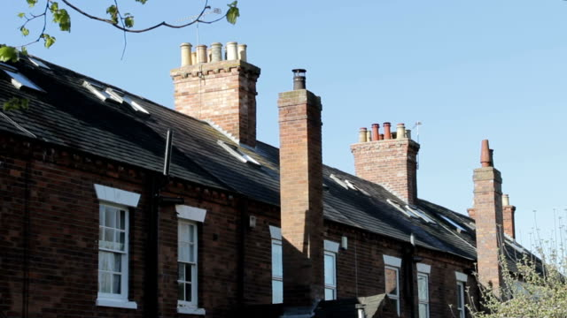 Chimneys, windows, slate tiled roof tops of traditional Victorian houses video