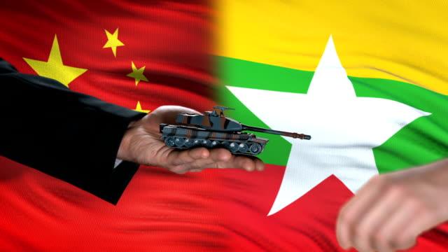funzionari di cina e myanmar che scambiano denaro dei carri armati, commercio di armi, sfondo della bandiera - naypyidaw video stock e b–roll