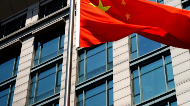 Bandera China ondeando contra edificio del negocio - vídeo